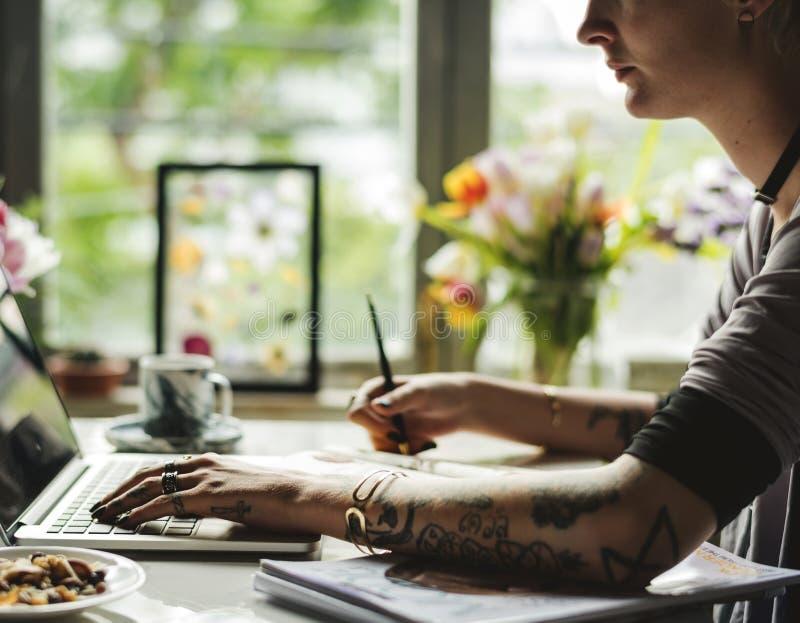 Mujer que usa su ordenador portátil para crear imagen de archivo libre de regalías