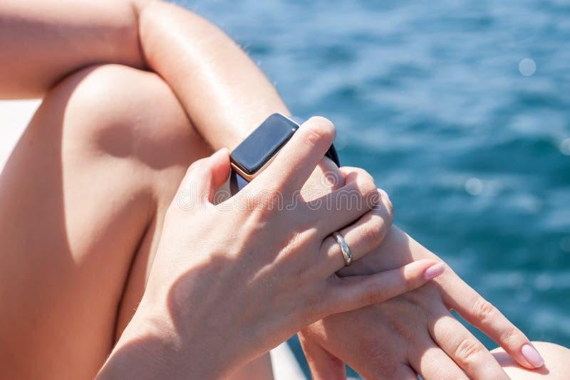 Mujer que usa su reloj elegante foto de archivo