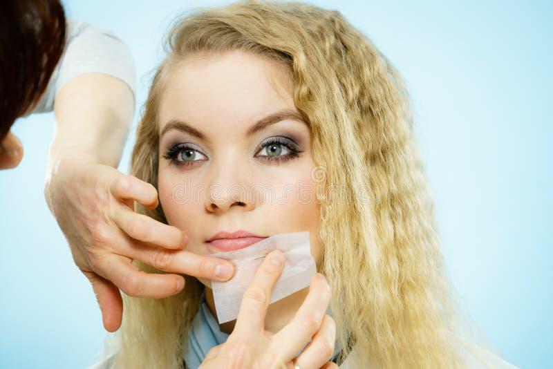 Mujer que usa tejidos que borran del aceite en modelo fotos de archivo