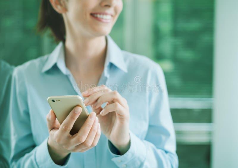 Mujer que usa un smartphone e inclinándose en una ventana fotografía de archivo libre de regalías
