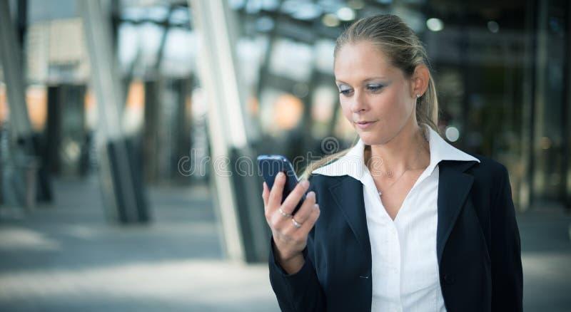 Mujer que usa un teléfono móvil foto de archivo libre de regalías