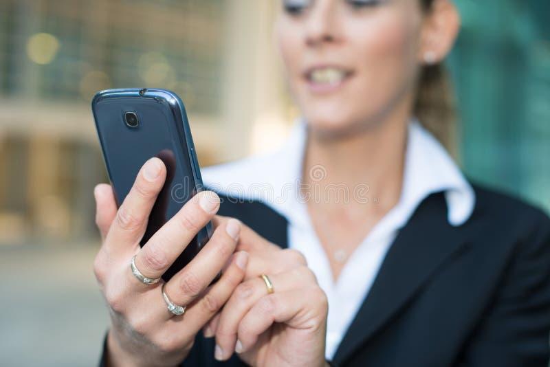Mujer que usa un teléfono móvil imagenes de archivo