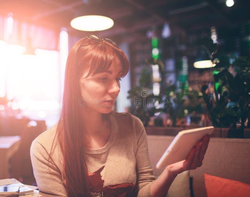 Mujer que usa un teléfono móvil en el restaurante, café, barra imagen de archivo