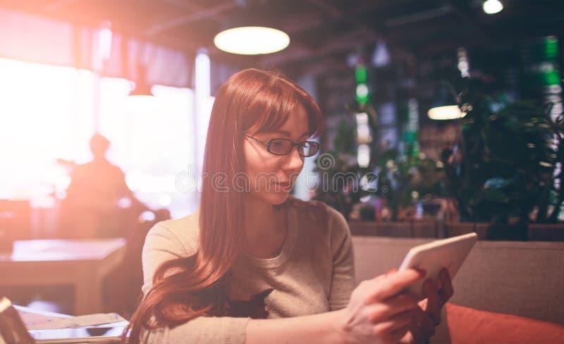 Mujer que usa un teléfono móvil en el restaurante, café, barra foto de archivo libre de regalías