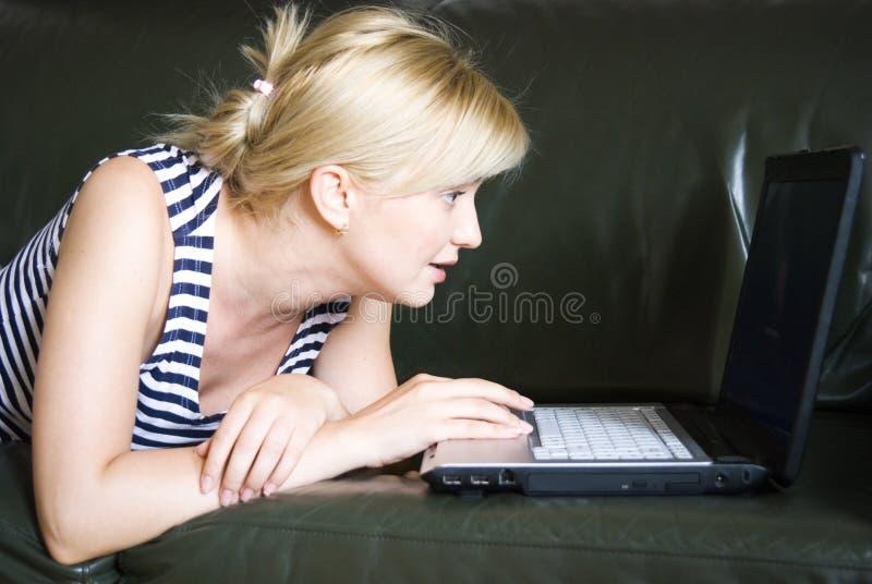 Mujer que usa una computadora portátil foto de archivo