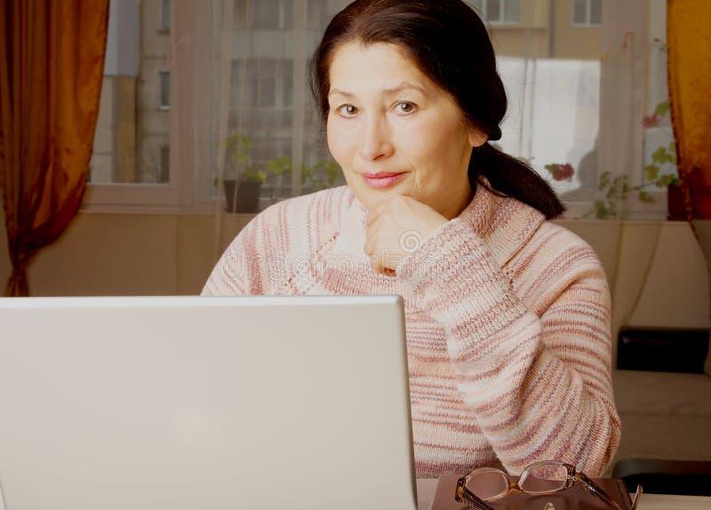 Mujer que usa una computadora portátil fotos de archivo