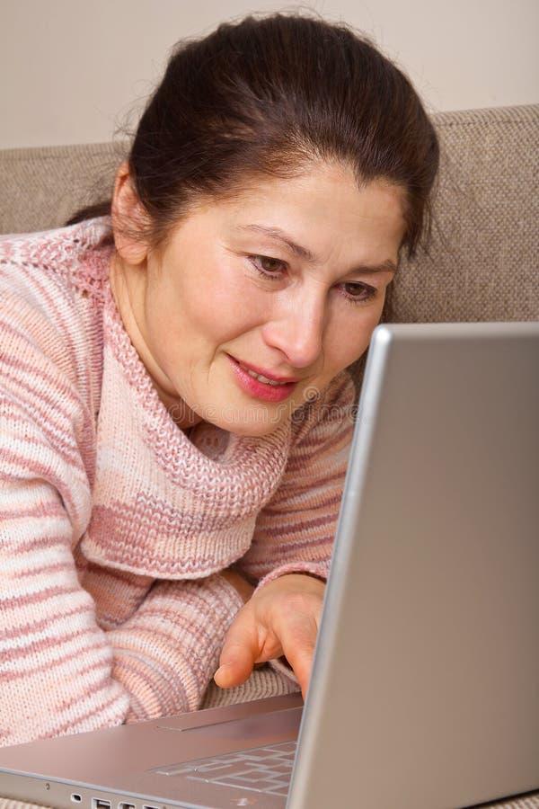 Mujer que usa una computadora portátil fotografía de archivo