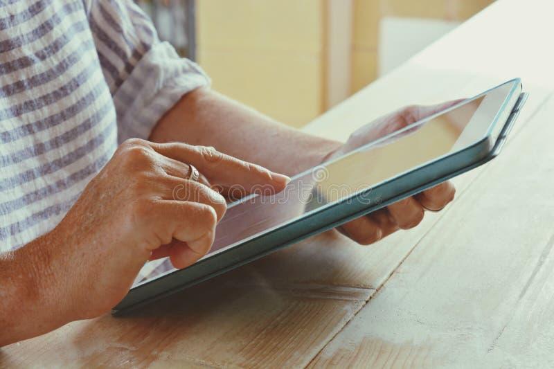Mujer que usa una tableta digital, finger en pantalla táctil fotos de archivo