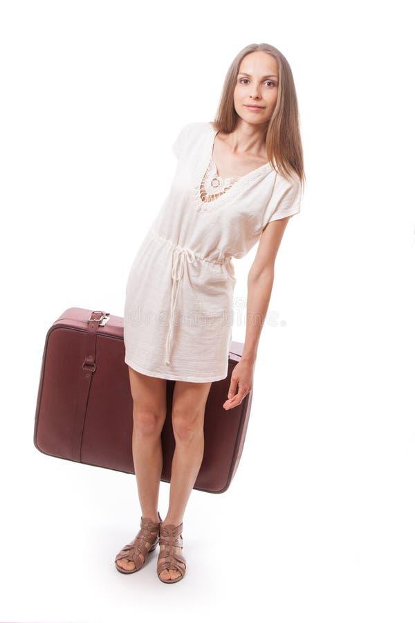 Mujer que va con la maleta pesada, aislada en blanco fotos de archivo libres de regalías