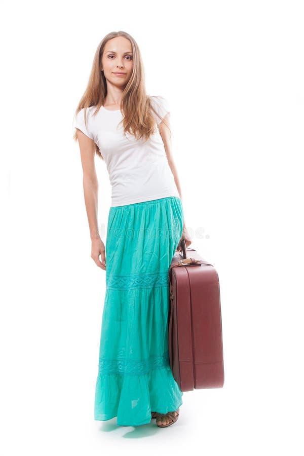Mujer que va con la maleta pesada, aislada en blanco imagen de archivo