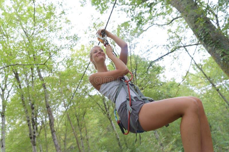Mujer que va en aventura del zipline de la selva fotografía de archivo libre de regalías