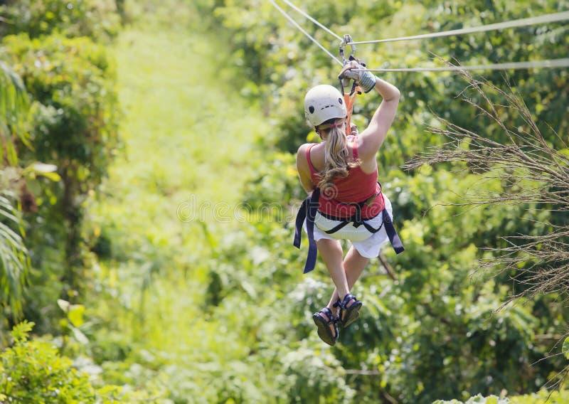 Mujer que va en una aventura del zipline de la selva foto de archivo