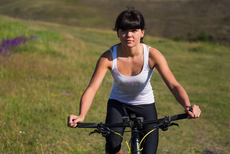Mujer que va para el paseo de la bici el día soleado en campo imagen de archivo libre de regalías