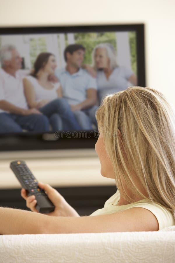 Mujer que ve la TV con pantalla grande en casa foto de archivo