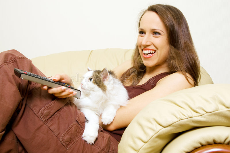 Mujer que ve la TV con su gato imágenes de archivo libres de regalías