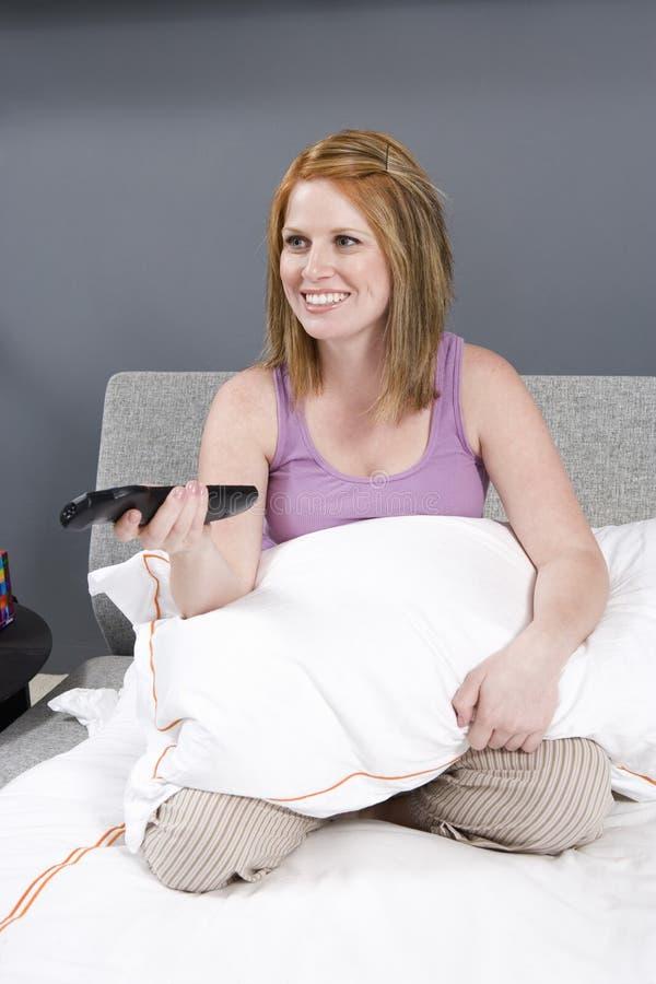 Mujer Que Ve La TV En Dormitorio Imagen de archivo