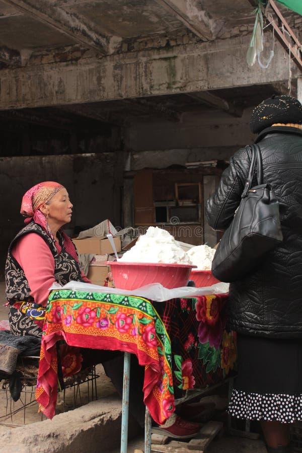 Mujer que vende el kashk en Osh imagen de archivo libre de regalías