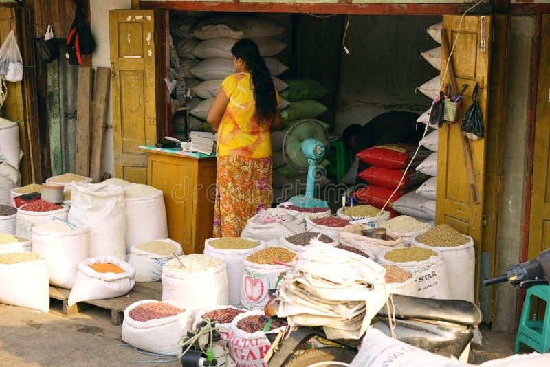 Mujer que vende el soporte Mandalay Rangún Myan del mercado de las habas del arroz de las mercancías fotografía de archivo