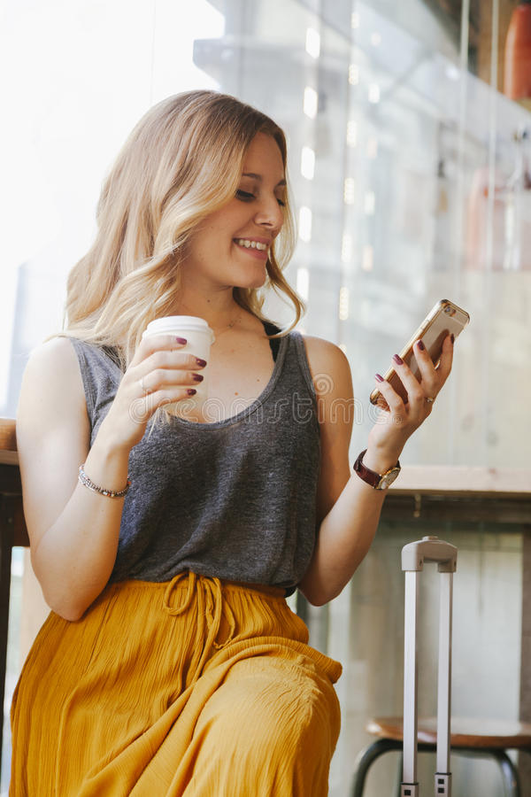 Mujer que viaja con un café de consumición de la maleta y que mira h imagen de archivo