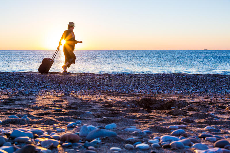 Mujer que viaja de la persona que camina en la playa del océano en la salida del sol fotos de archivo libres de regalías