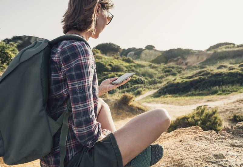 Mujer que viaja en una pista de senderismo usando smartphone, viaje y concepto activo de la forma de vida foto de archivo