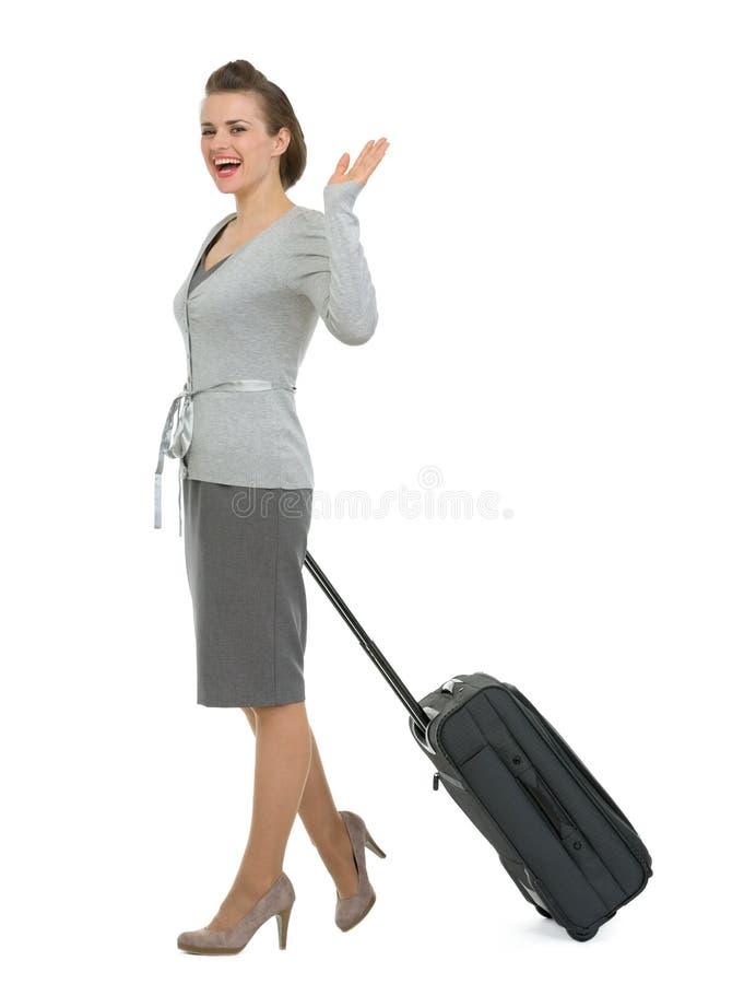 Mujer que viaja feliz con la mano que agita de la maleta fotos de archivo libres de regalías
