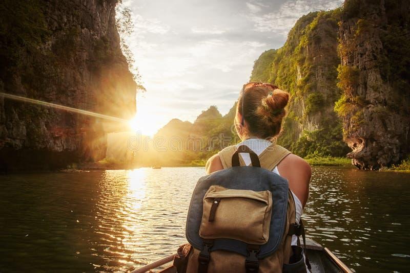 Mujer que viaja por el barco que disfruta de puesta del sol entre de las montañas del karst fotografía de archivo