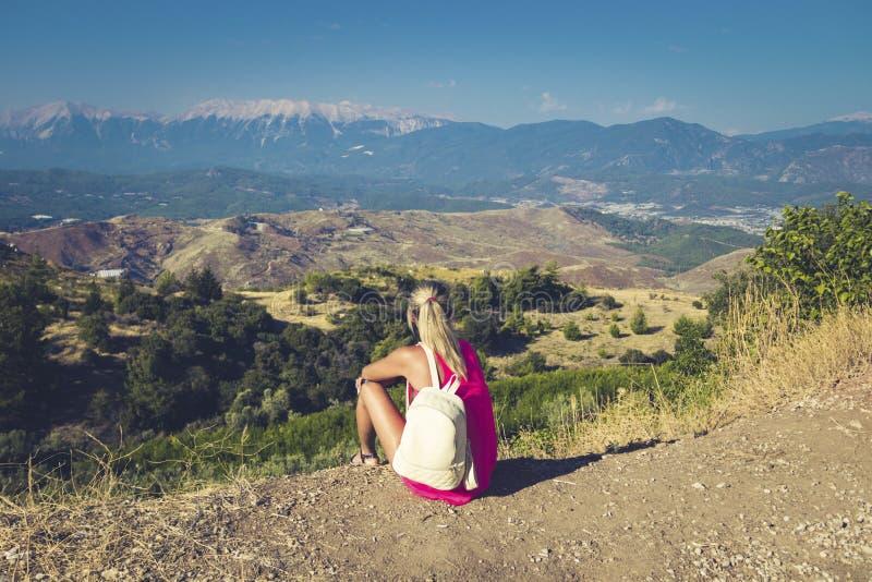 Mujer que viaja que se sienta cerca de la montaña y que mira lejos imagen de archivo libre de regalías