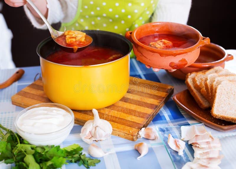 Mujer que vierte la sopa de remolachas rusa tradicional imagen de archivo