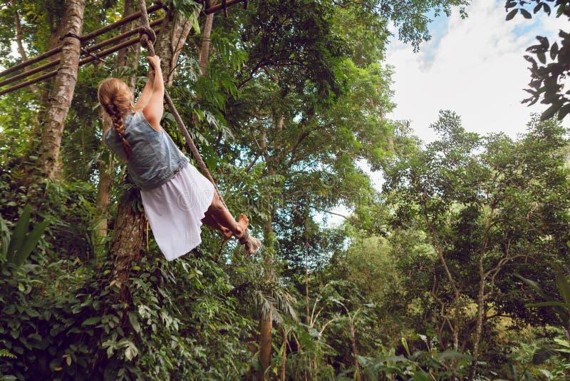 Mujer que vuela arriba en el oscilación de la cuerda en fondo salvaje de la selva imagenes de archivo
