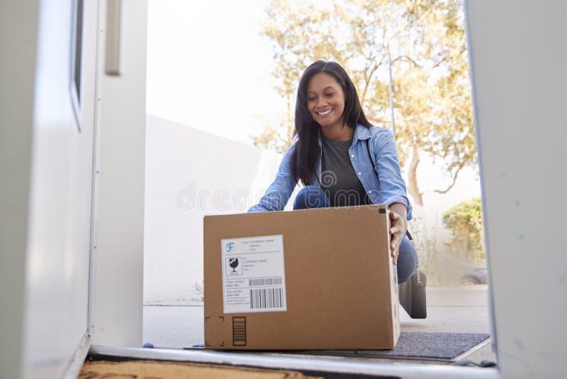 Mujer que vuelve al servicio a domicilio en caja de cartón fuera de Front Door fotos de archivo