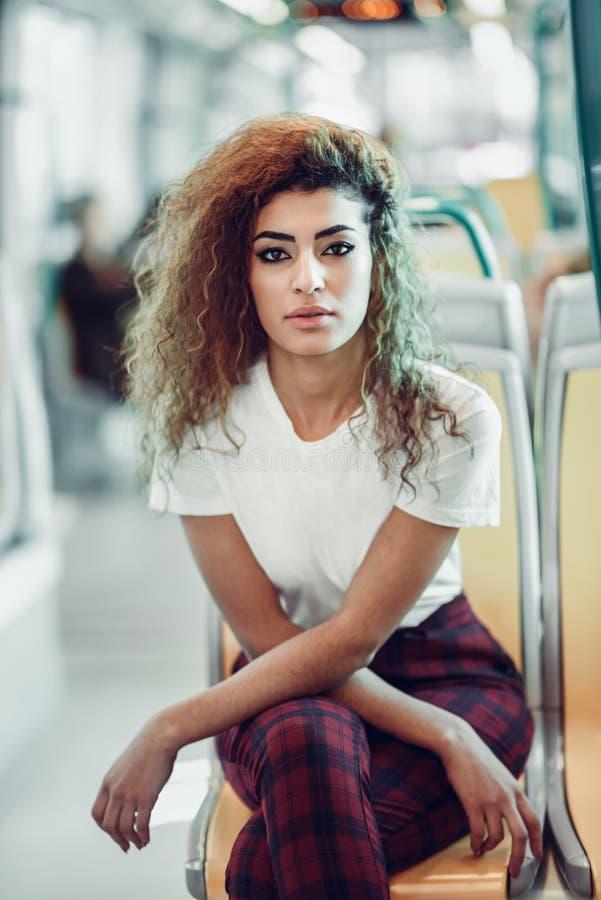 Mujer ?rabe dentro del tren del metro Muchacha ?rabe en ropa casual imagen de archivo
