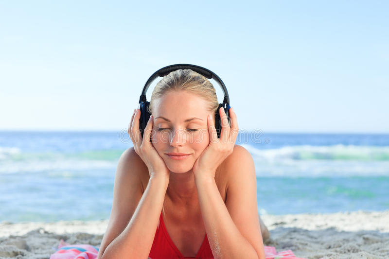 Mujer radiante que escucha una cierta música fotografía de archivo libre de regalías