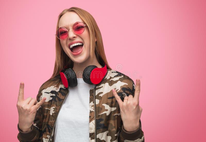 Mujer rebelde elegante en gafas de sol y auriculares fotografía de archivo