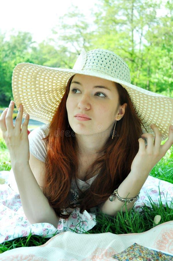 Mujer redheaded pensativa que mira lejos en un sombrero blanco del verano al aire libre fotos de archivo