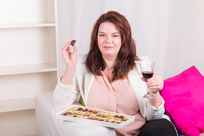 Mujer regordeta en casa que come los chocolates y que bebe el vino imagenes de archivo