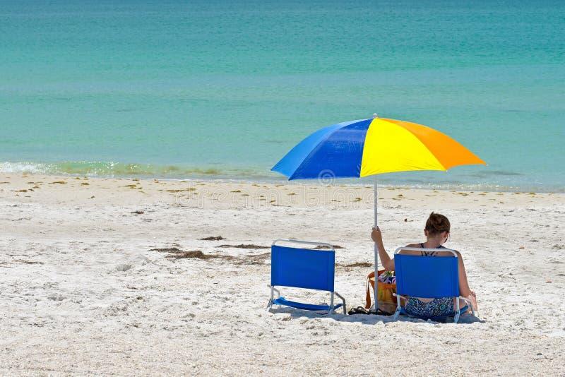 Mujer relajándose en la playa fotos de archivo