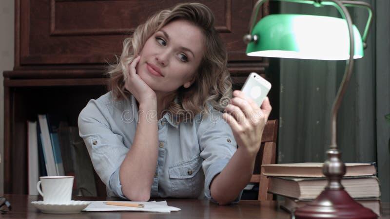 Mujer relajada del youn que se sienta en la tabla con los libros y que toma selfies divertidos con su teléfono fotografía de archivo