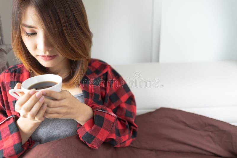 Mujer relajada en cama con la taza de café en manos, visión superior mañana, ocio, concepto de la gente - café de consumición fel foto de archivo