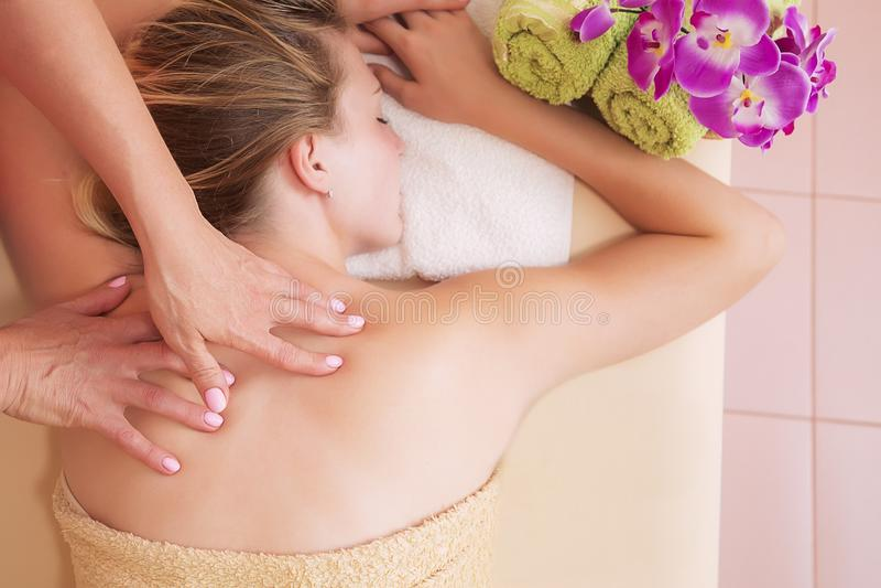 Mujer relajada en la tabla del masaje que recibe el tratamiento de la belleza en el balneario del día fotografía de archivo
