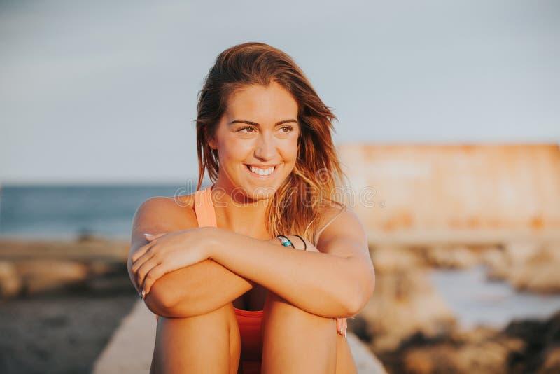 Mujer relajada en ropa de deportes en la costa imagenes de archivo