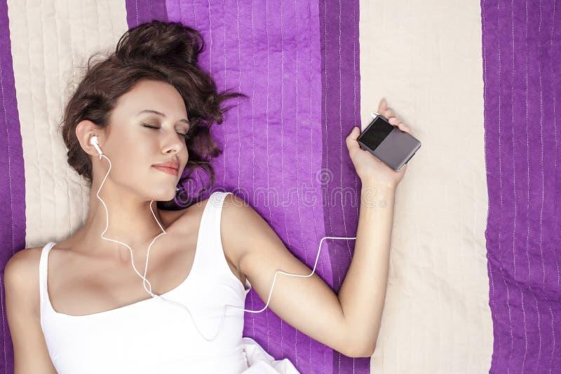 Mujer relajada que escucha la música con reproductor Mp3 usando los auriculares mientras que miente en la manta de la comida camp imagen de archivo libre de regalías