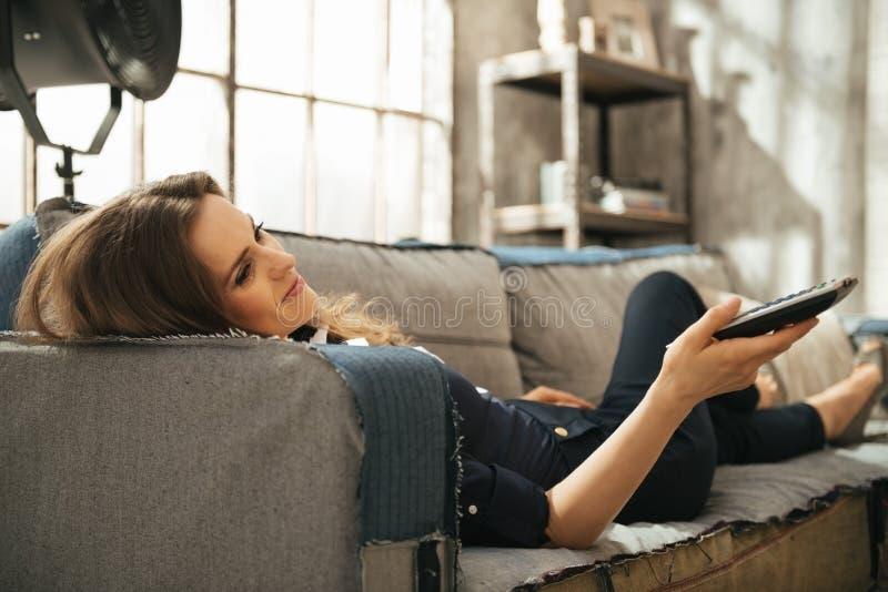 Mujer relajada que miente en el sofá y la TV de observación en el apartamento del desván imagen de archivo