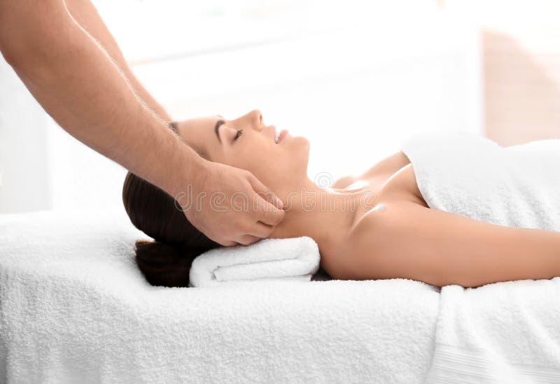 Mujer relajada que recibe masaje del cuello imagen de archivo