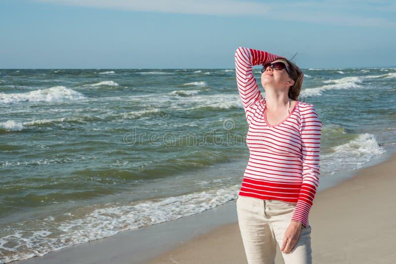 Mujer relajada que se coloca cerca del mar foto de archivo libre de regalías