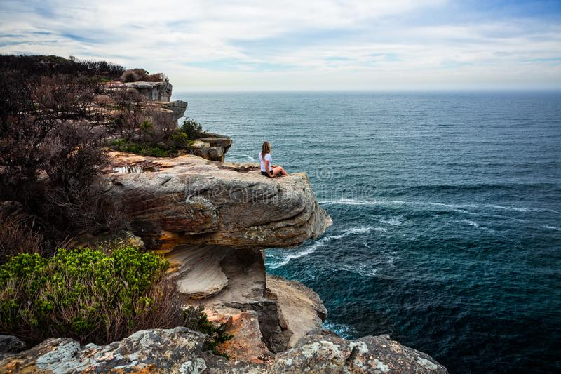 Mujer relajada que se sienta en el promontorio costero que mira hacia fuera al océano imagen de archivo libre de regalías