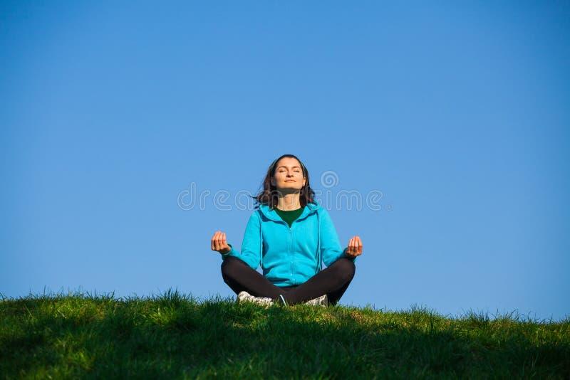 Mujer relajada que se sienta en la posición de loto fotos de archivo