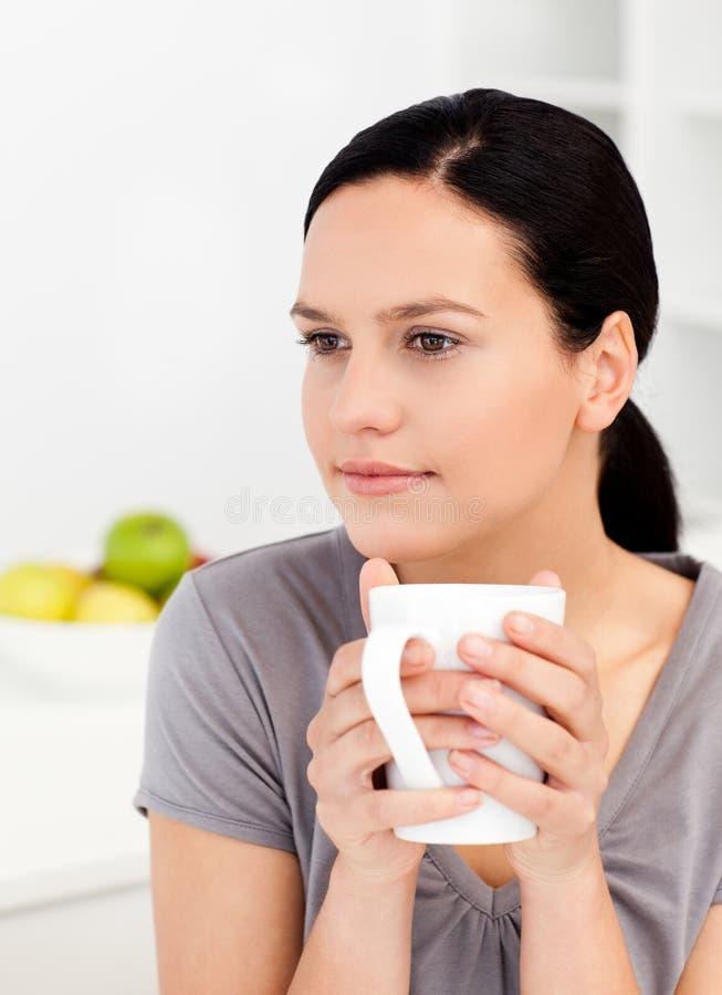 Mujer reservada que bebe su café en la cocina imagenes de archivo