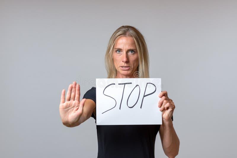 Mujer resuelta que soporta una muestra de la parada fotos de archivo libres de regalías