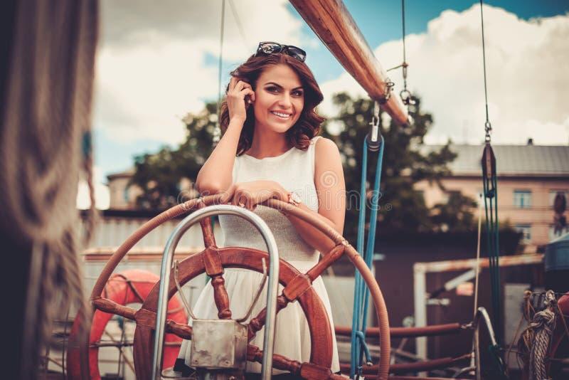 Mujer rica elegante en una regata de madera de lujo imagenes de archivo